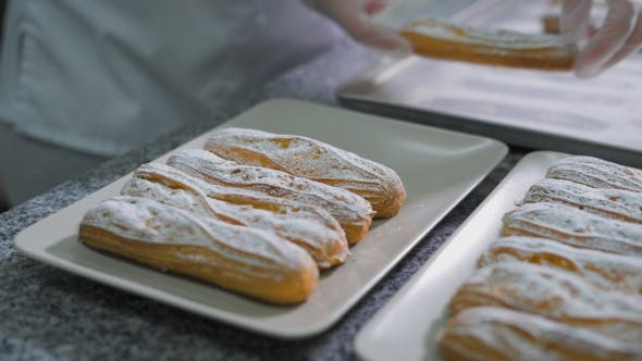 Thumbnail for Baker By Hands Neatly Folded Freshly Baked Eclairs with Sugar Powder on a Beautiful White Plates