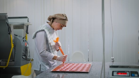 Thumbnail for Kind of a Young Confectioner Woman Who Is Standing Sideways in the Confectionery Factory