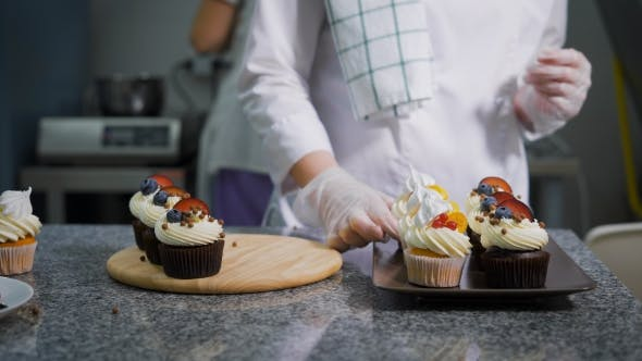 Thumbnail for The Process of How To Cook Pastry Chef Puts on a Small Metallic Tray of Cupcakes with White Butter