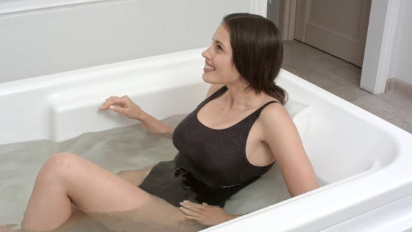 Thumbnail for Young Woman Getting Into Spa Bath