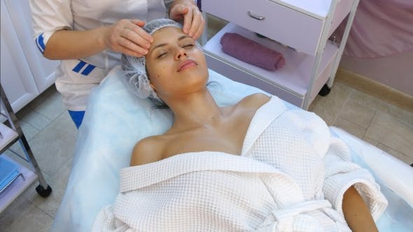 Thumbnail for Beautiful Young Woman Receiving Facial Massage with Closed Eyes in a Spa Salon.