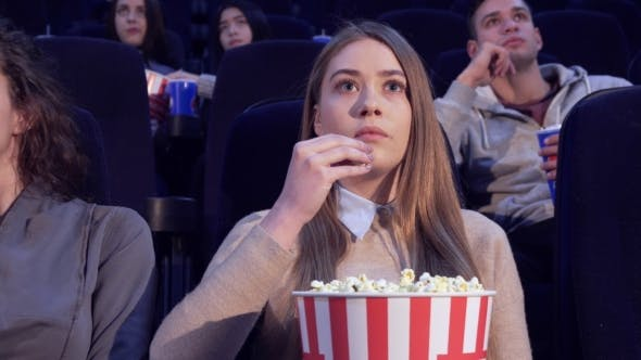 Thumbnail for Girl Slowly Puts the Popcorn in Her Mouth at the Movie Theater