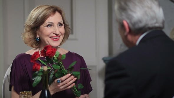 Thumbnail for Smiling Senior Woman Receiving Flowers From Man