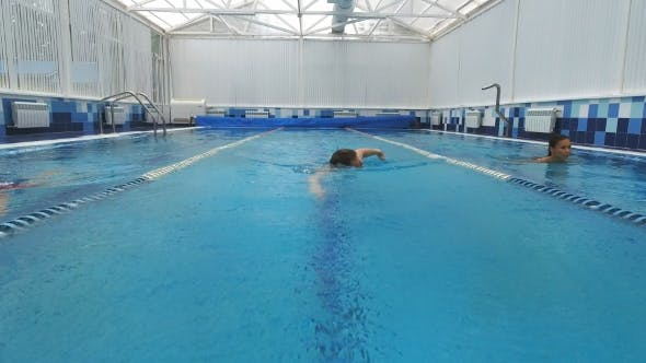Thumbnail for Two Smiling Young Women Swimming in Different Pool Lanes with a Young Man Swimming Crawl