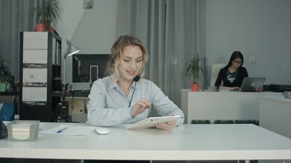 Thumbnail for Focused Call Center Agent Using Digital Tablet at Her Workplace