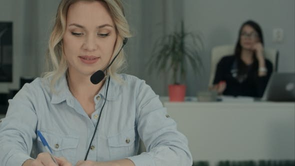 Thumbnail for Smiling Female Consultant with Headset Making Notes While Her Coworker Taking Selfies