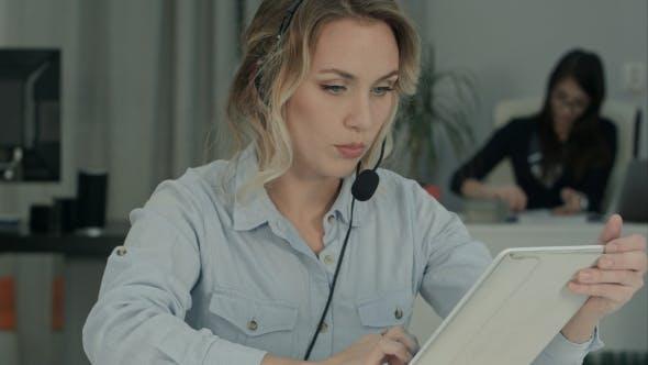 Thumbnail for Busy Call Center Agent mit digitalem Tablet bei einem Anruf an ihrem Arbeitsplatz