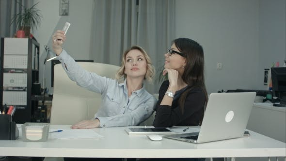 Cover Image for Two Female Colleagues Taking Selfie with Phone in the Office