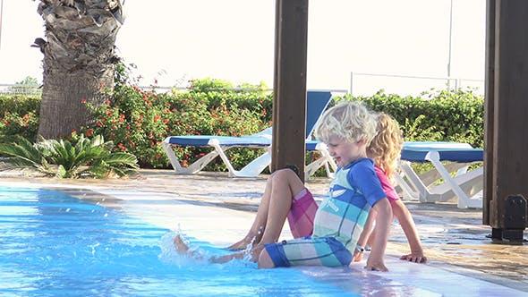Thumbnail for Spielerische Kinder sitzen auf dem Rand des Pools baumeln Füße in Wasser