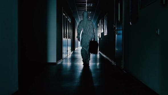 Cover Image for The Scientist in Protective Suit and with Bag Going Through the Corridor