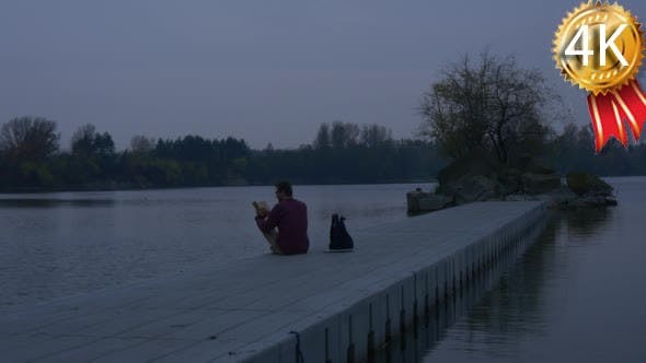 Man Reads a Book in Evening on Concrete Pier