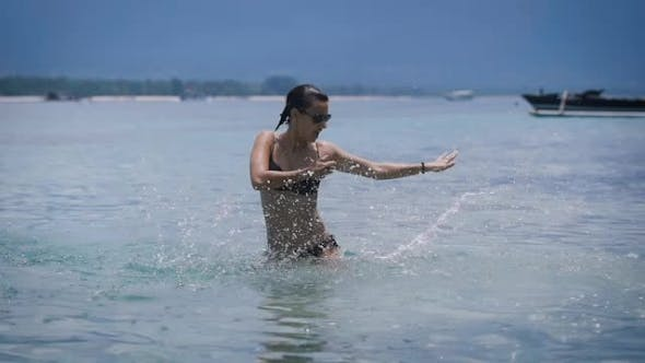 Thumbnail for Sexy Brunnete in Black Bikini Dancing and Splashing with Water in the Ocean on the Beach of Bali