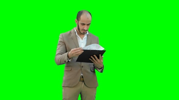 Thumbnail for Concentrated Businessman Reading Financial Report on a Green Screen, Chroma Key