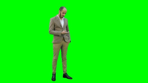 Thumbnail for Young Man in Suit Sending Text Messages on His Phone on a Green Screen, Chroma Key.