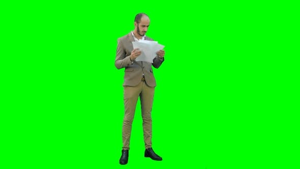 Thumbnail for Serious Young Manager Standing and Reading Documents