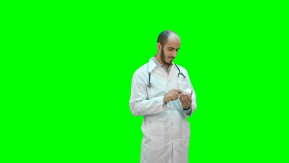 Thumbnail for Male Doctor Attentively Reading Medicine Label of a Bottle of Pills on a Green Screen, Chroma Key.
