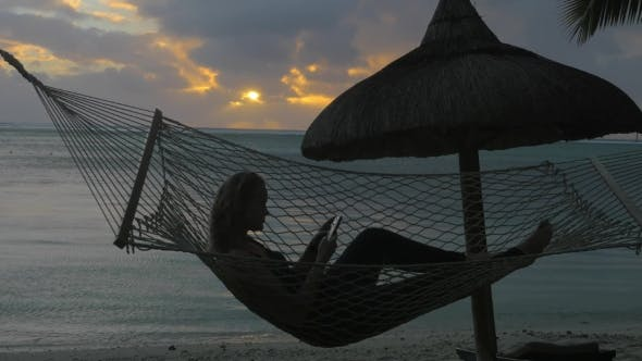 Thumbnail for Woman with Phone Lying in Hammock on the Beach
