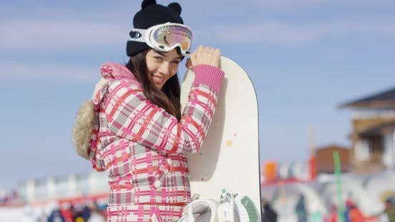 Thumbnail for Cute Asian Female Snowboarder Relaxing on Slope