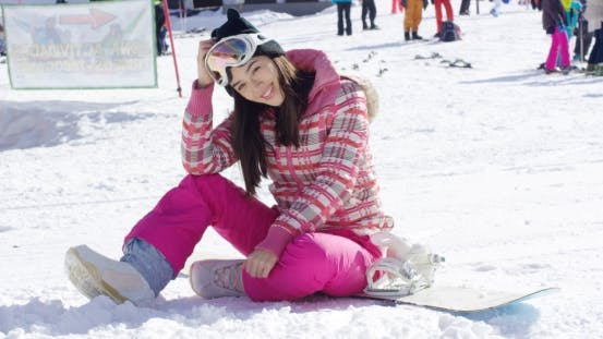 Thumbnail for Woman in Pink Snowsuit with Snowboard