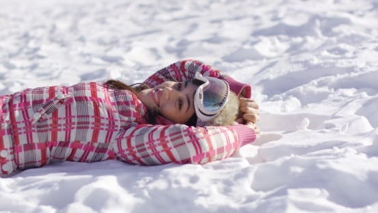 Thumbnail for Young Woman Lying on Snow with Ski Goggles