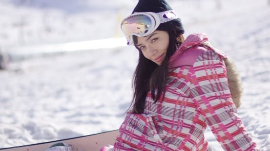 Thumbnail for Beautiful Asian Snowboarder Sitting on Snow