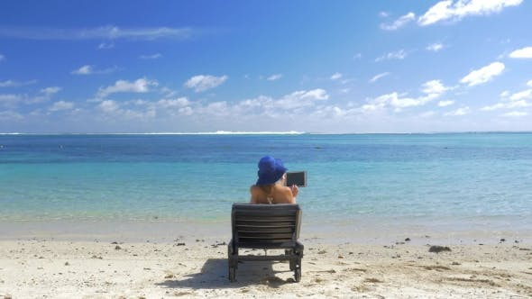 Thumbnail for Woman with Pad Sun Bathing on the Coast of Blue Lagoon