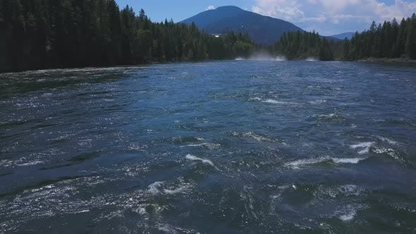 Thumbnail for Aerial Drone Traveling Low Along Flowing Water With Mountains In Background 1