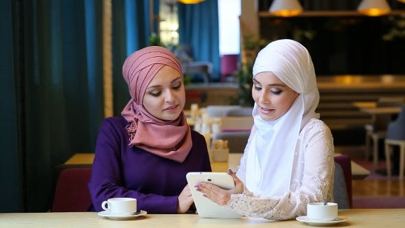 Thumbnail for Two Beautiful Muslim Girl Using Tablet In Cafe