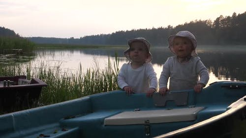 Cute Twins in Bucket Hats Happily Playing with a Boat at the Lake, Special Moments of Life
