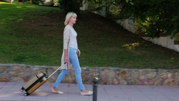Thumbnail for Woman with Travel Bag Goes Down the Resort Area. On a Clear Sunny Day