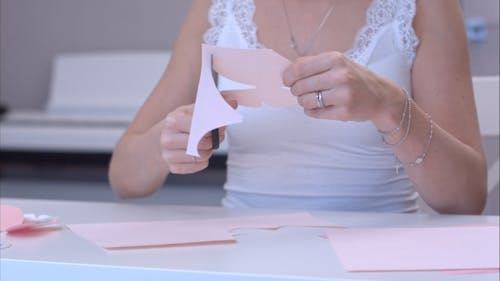 Young Woman Cutting Out Paper Butterfly