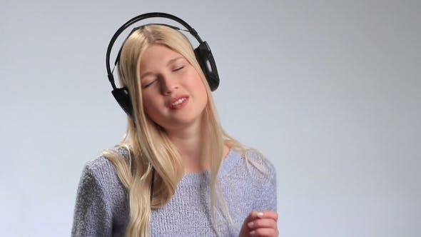 Thumbnail for Emotional Young Blonde in Headphones Over White