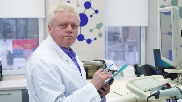 Male Scientist Notes Information on Clipboard at the Laboratory