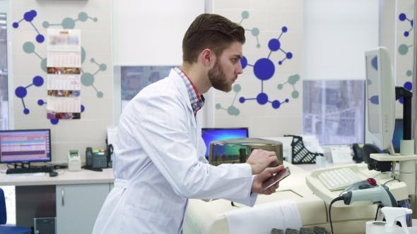 Thumbnail for Man Enters Information From Computer To the Tablet at the Laboratory