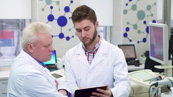 Thumbnail for Male Scientist Shows Something on His Tablet To His Coworker at the Laboratory