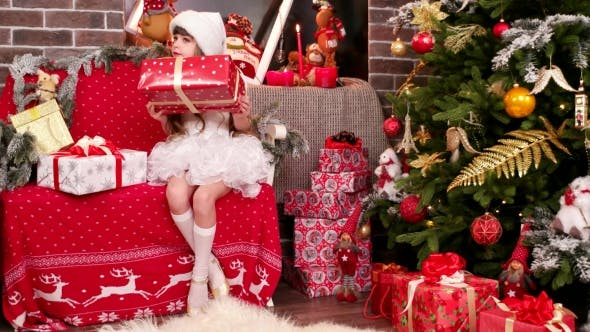 Cover Image for Gift Wrapping, a Little Girl Lays Out Name Cards for Christmas Gifts