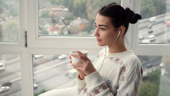 Thumbnail for Charming Young Woman in Earphones Sitting Near Window Listening Musik and Drink Coffee