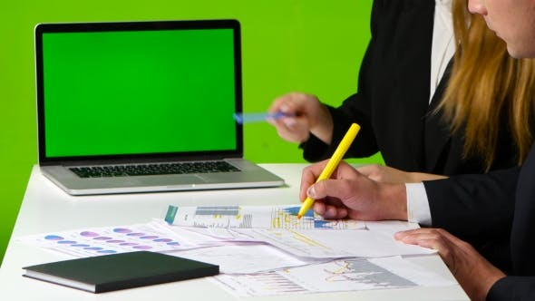 Cover Image for Man and Woman Draw a Graph. Work with Green Screen Monitor in the Office