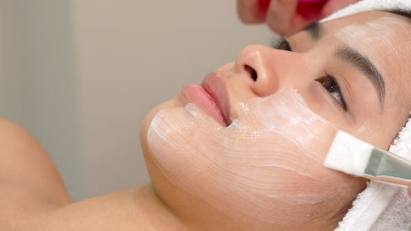 Thumbnail for Beauty Specialist Uses Brush To Apply Cosmetic Mask on Girl's Face