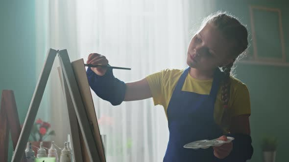 Beautiful Girl In Blue Apron Is Painting