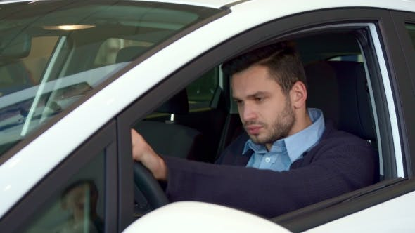 Cover Image for Man Sits Into the Car at the Dealership