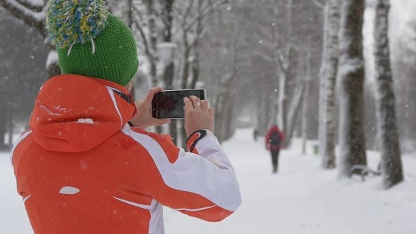 Thumbnail for Woman Takes Pictures of Snowfall on Smartphone