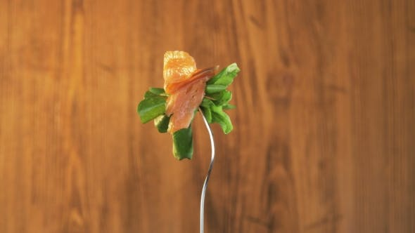 Thumbnail for Rotating Fork With Salmon and Lettuce on Wooden Background