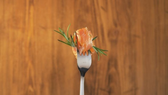 Thumbnail for Rotating Fork With Salmon and Rosemary on Wooden Background