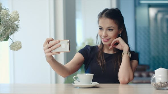 Smiling Young Woman Taking Selfies on Her Phone at the Cafe
