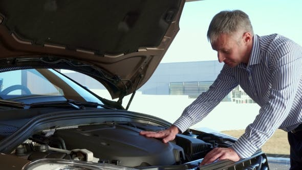 Thumbnail for Mature Man Looks at the Car Engine at the Dealership