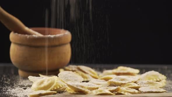 Schmackhafte Ravioli mit Mehl und Basilikum auf Holztisch