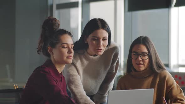 Female Coworkers Discussing Project on Laptop
