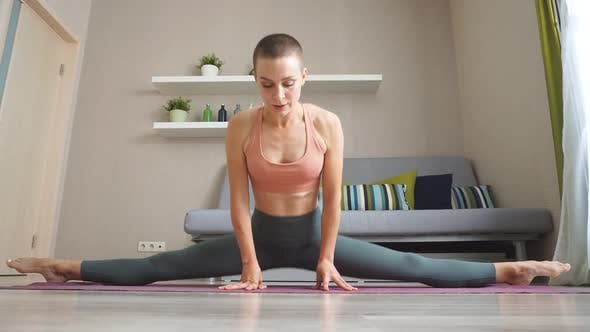 Young Woman Training Yoga at Home Sitting on Mat and Stretching Muscles of Legs.