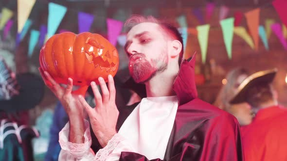 Man in Vampire Outfit Holds a Carved Pumpkin Head in His Hand